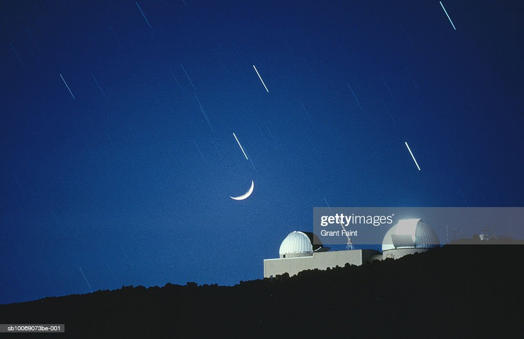 Moon crescent and star trails over observatory, blurred motion : Stockfoto