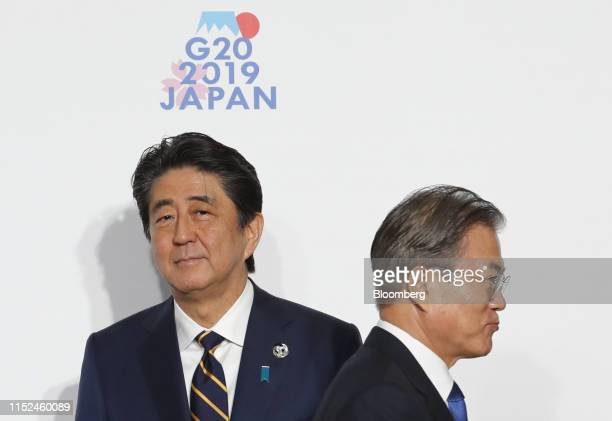 Moon Jae-in, South Korea's president, right, walks past Shinzo Abe, Japan's prime minister, prior to a family photo session at the Group of 20 summit...