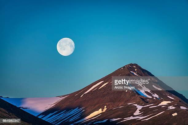 Moon over glacial mountain ridge