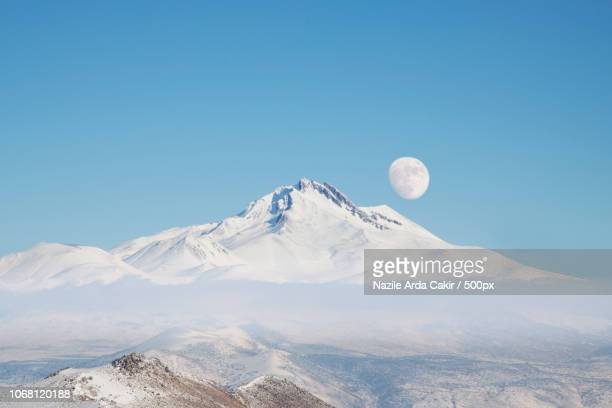moon over mountain peak - snow moon stock pictures, royalty-free photos & images