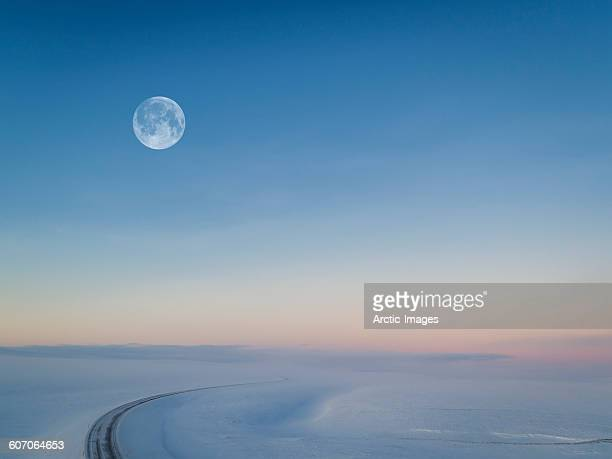 moon over snowy road, iceland - pleine lune photos et images de collection