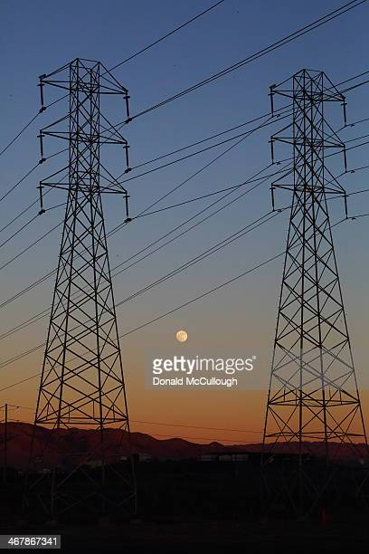 Moon rise among the high voltage lines in the east bay . The colors of the Belt of Venus give it a twilight feeling. The moon is a day before full.