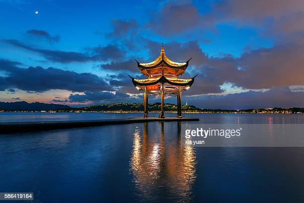 Moon rises in night sky as clouds pass over the West lake,Hangzhou,China