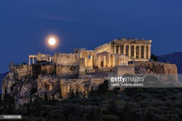 moon rising behind the acropolis - column stock pictures, royalty-free photos & images