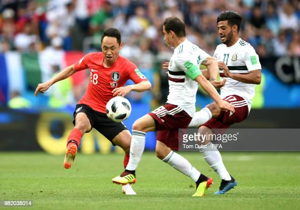 Moon SeonMin is tackled by Andres Guardado and Carlos Vela of Mexico during the 2018 FIFA World Cup Russia group F match between Korea Republic and...