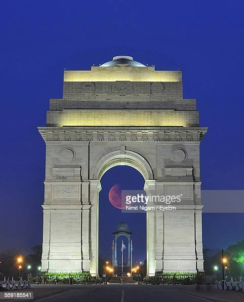 moon viewed through arch of india gate - india gate stock pictures, royalty-free photos & images