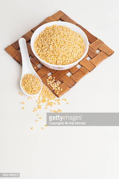 Moong dal in a bowl isolated on white background with spoon and table mat