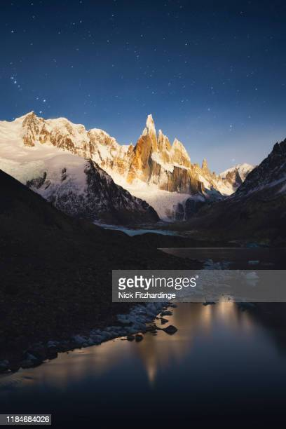 moonlight on cerro torre reflected in laguna torre, los glaciares national park, argentina - cerro torre stock-fotos und bilder