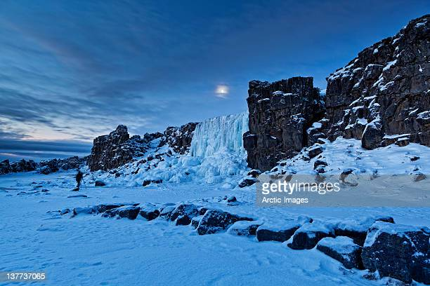 moonlight over frozen waterfalls and lava. - pingvellir national park stock photos and pictures