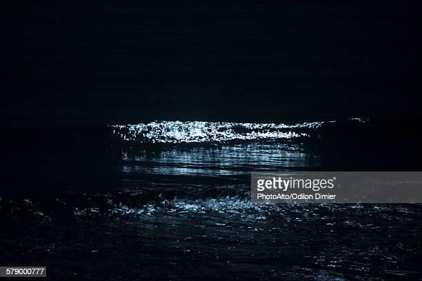Moonlight reflecting on ocean waves at night