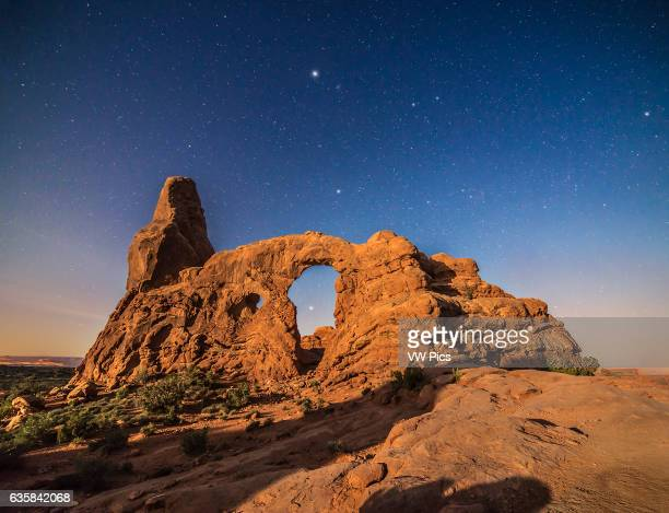 A moonlit scene at Turret Arch in Arches National Park Utah with Sirius shining through the Arch Procyon above the Arch and above it at top centre...