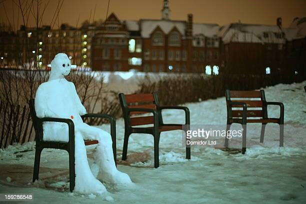 CONTENT] A moonlit snowman on a chair in a London park at night