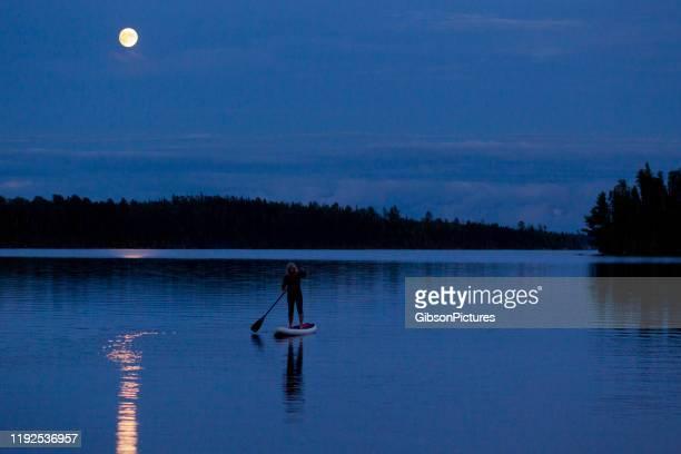 moonlit stand up paddleboard abenteuer - one night stand stock-fotos und bilder