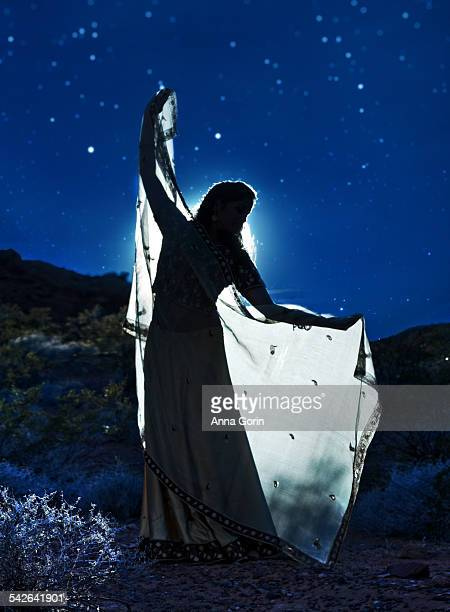 Moonlit woman in desert with outstretched shawl
