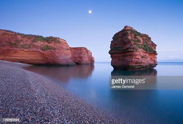 moonrise over ladram bay at dusk. jurassic coast world heritage site. devon. england. uk. - jurassic coast stock pictures, royalty-free photos & images