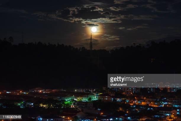 moon-rise over sub-urban area in kuala lumpur, malaysia - shaifulzamri stockfoto's en -beelden