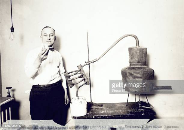 Moonshine still recently confiscated by the Internal Revenue Bureau photographed at the Treasury Department. Man standing next to still looking at...