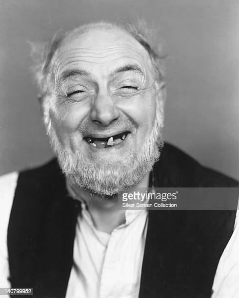 Moore Marriott , British actor, smiling with a toothless grin, wearing a black waistcoat over a white shirt in a studio portrait, circa 1940.