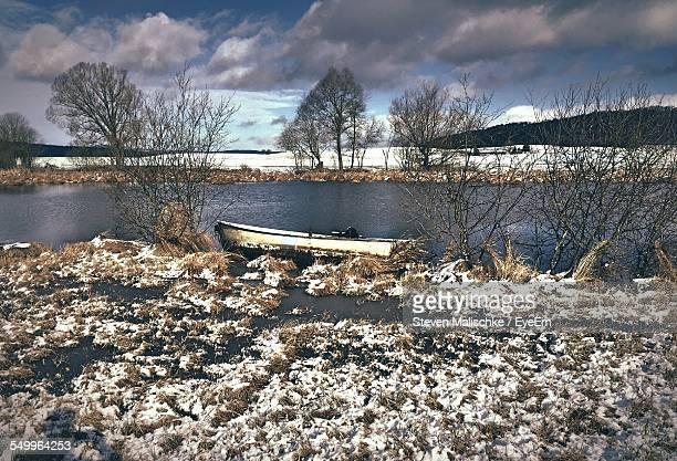 Moored Boat In Calm Lake On Snowed Landscape