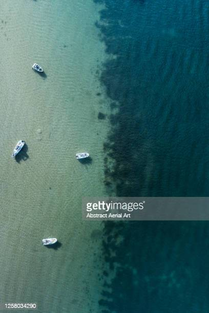 moored boats in shallow water seen from directly above, dorset, england, united kingdom - exploration stock pictures, royalty-free photos & images