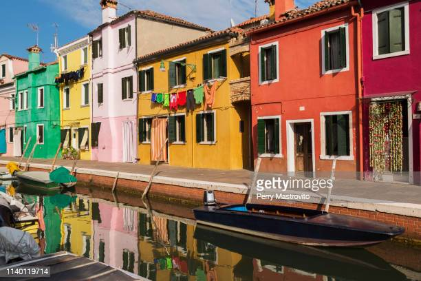 moored boats on canal lined with pink, red, orange, yellow and green stucco houses decorated with curtains, washed clothes on clothesline, burano island, venetian lagoon, veneto, italy - burano foto e immagini stock