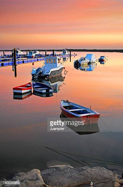Moored boats on sea at sunset