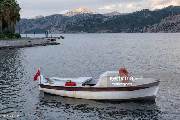 moored fishing boat at the foreground and man fishing at the background on a wooden pier in selimiye bay. - emreturanphoto stock-fotos und bilder