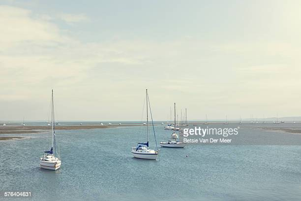 moored sailing boats in sea - keyhaven stock photos and pictures