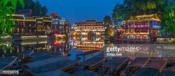 Moored sampan boats in front of illuminated town houses at dusk, Fenghuang, Hunan, China