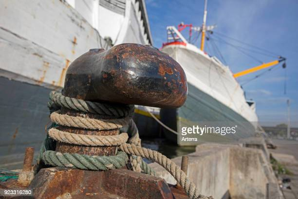 Mooring rope of wooden pinisi phinisi traditional Indonesian cargo ship tied around shoreside bitt in the port of Semarang Java Indonesia