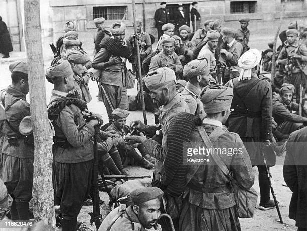 Moorish troops who are fighting with the antiCommunist forces pictured as they rest after a victorius encounter in the Spanish Civil War in a suburb...