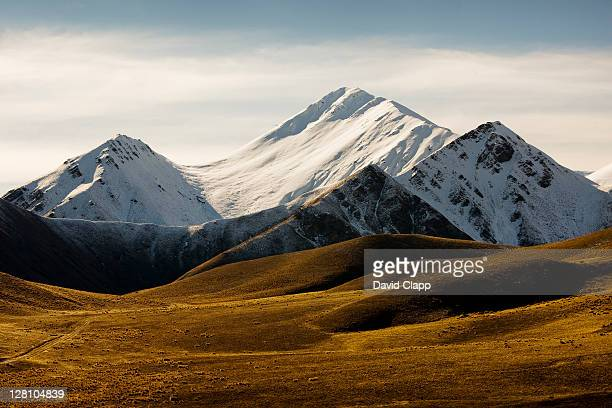 moorland and snow capped mountains at lindis pass, south island, new zealand - land geografisches gebiet stock-fotos und bilder