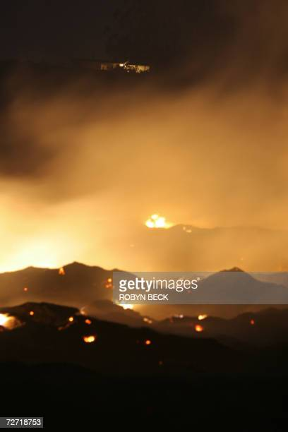 Embers from the Shekell fire smolder below a home 04 December 2006 in Moorpark California approximately 50 miles northwest of Los Angeles Hot Santa...