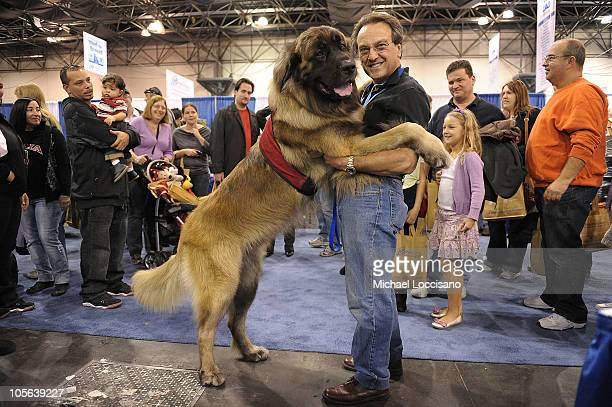 Moose a Leonberger and Dr Joe embrace during the second annual Meet the Breeds showcase of cats and dogs at the Jacob K Javits Convention Center on...