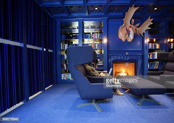 A moose sculpture hangs on the wall while an employee works near a fireplace in a common area of Google Canada's engineering headquarters in Waterloo...