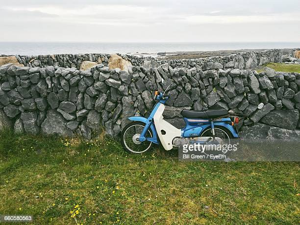 moped leaning on stone wall against sky - mobylette photos et images de collection