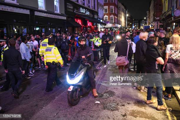 Moped rider is seen driving through heavy crowds in Soho on July 4, 2020 in London, United Kingdom. The UK Government announced that Pubs, Hotels and...
