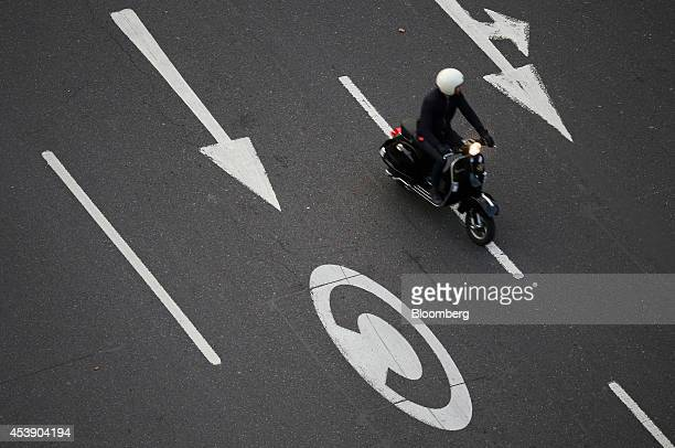 A moped rider passes a road sign denoting the start of the congestion charge a fee levied on cars entering part of the central city as it drives...