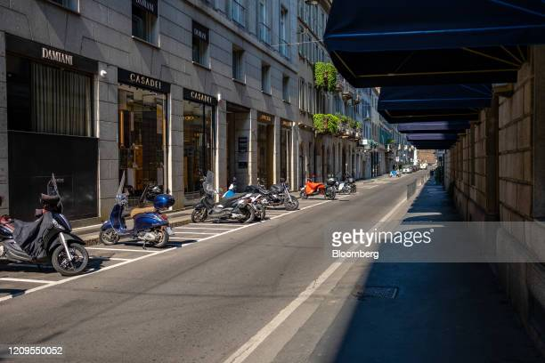 Mopeds sit parked outside closed luxury boutiques on Via Monte Napoleone the fashion district artery in Milan Italy on Wednesday April 8 2020 Italy...