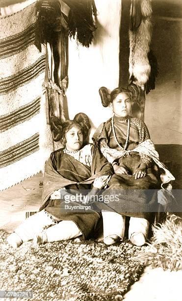 Moqui Indian girls of Oraibi Moqui Arizona posed seated fulllength wearing native dress 1898