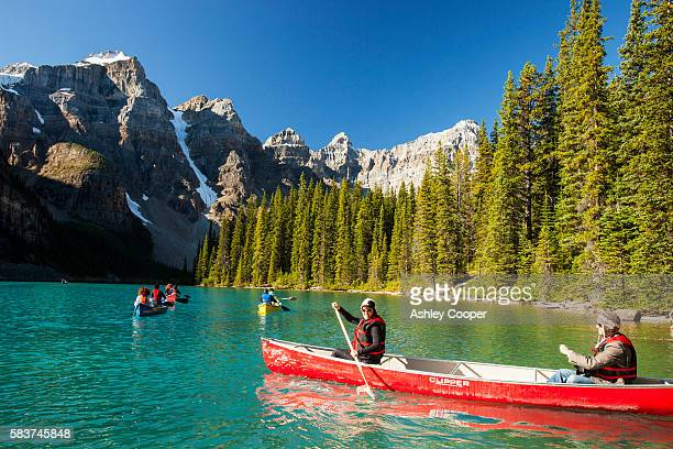 Moraine Lake in the Canadian Rockies is one of the most picturesque, beautiful places in the whole of the Rocky mountains. The green/blue colour of the water is caused by rock flour, from glaciers reflecting diffrent colour wavelengths.