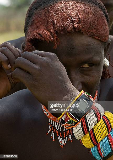 A moran warrior from the Samburu tribe disentangles his hair locks with the help of a peer inorder to clean and rearrange them on July 16 2013 in...