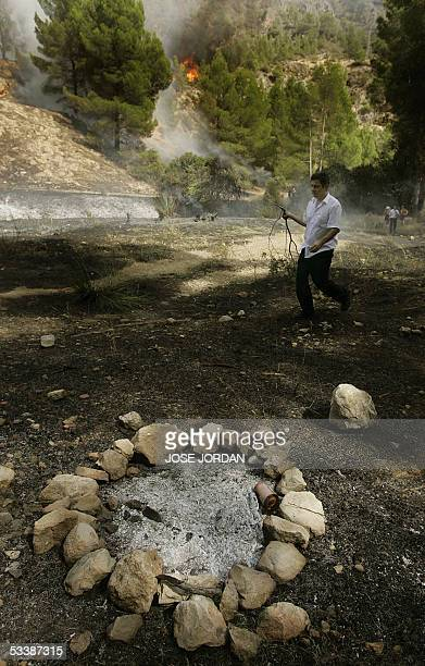 A man passes the campfire site which reportedly started a forest fire in Moratalla Murcia 14 August 2005 Thirteen Spanish firefighters have died...