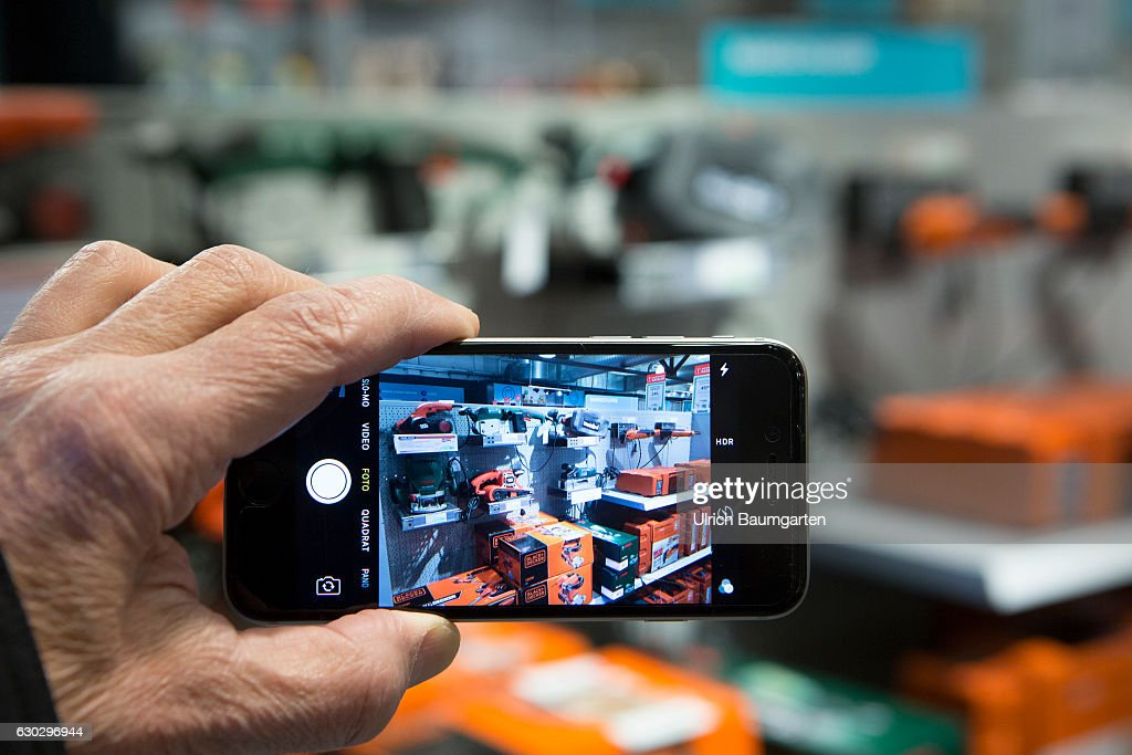 Mobile photo for the purpose of the price comparison in the Internet in a hardware store. : News Photo