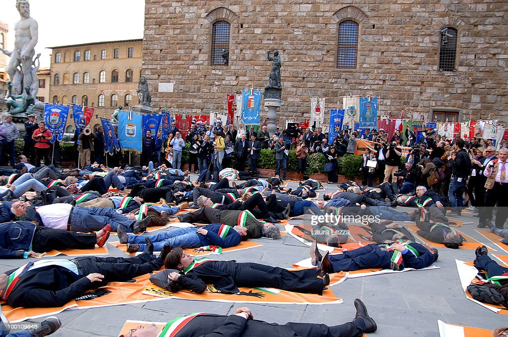 More than 100 of Central Italy's mayors protest against the Berlusconi Government with a Flash Mob in the Piazza della Signoria on May 20, 2010 in Florence, Italy. Mayors of Central Italy have declared a major emergency of Commons because of the cuts and the rigidity of the Stability Pact asking the Government to loosen budget constraints. The mayors wearing tricolor sashes marched through the streets of Florence and then lay on banners reading ' Thay are knocking your municipality to the ground'