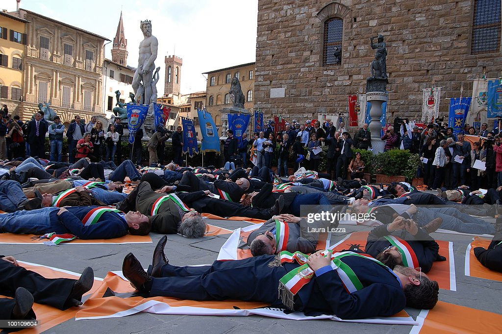 More than 100 of Central Italy's mayors protest against the Berlusconi Government with a Flash Mob in the Piazza della Signoria on May 20, 2010 in Florence, Italy. Mayors of Central Italy have declared a major emergency of Commons because of the cuts and the rigidity of the Stability Pact asking the Government to loosen budget constraints. The mayors wearing tricolor sashes marched through the streets of Florence and then lay on banners reading 'They are knocking your municipality to the ground.'