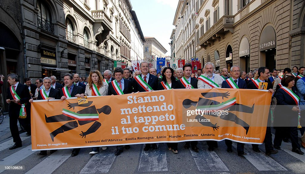 More than 100 of Central Italy's mayors protest against the Berlusconi Government as they parade through the streets with a banner that reads 'They are knocking your municipality to the ground' on May 20, 2010 in Florence, Italy. Mayors of Central Italy have declared a major emergency of Commons because of the cuts and the rigidity of the Stability Pact asking the Government to loosen budget constraints. The mayors wearing tricolor sashes marched through the streets of Florence and then lay for a Flash Mob in the Piazza della Signoria.