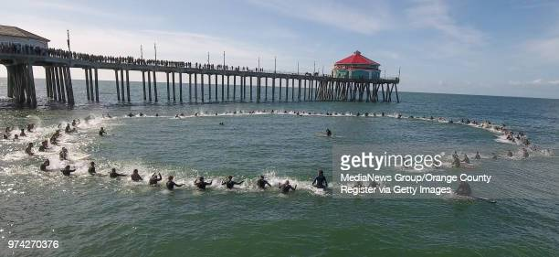 More than 100 surfers pound on their boards as they splash in honor of Pierre Agnes CEO of Quiksilver during a paddle out north of the Huntington...