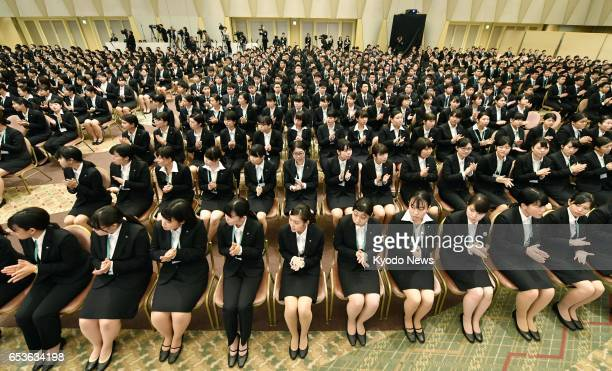 More than 1200 new recruits of 22 group companies of retail giant Seven i Holdings Co attend a welcoming ceremony at a hotel in Tokyo on March 16...