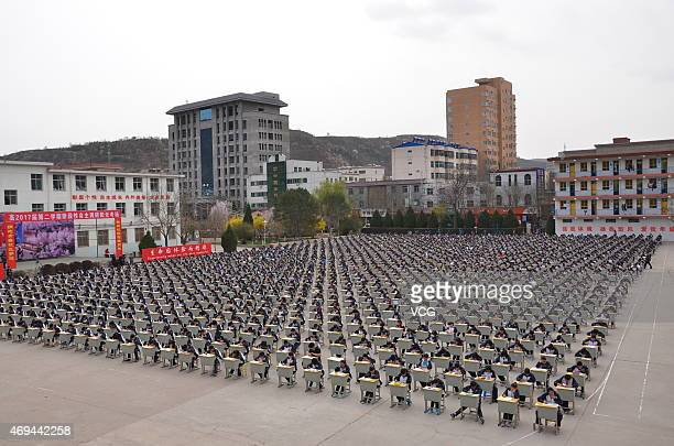 YAN'AN CHINA APRIL 11 More Than 1700 students of Yichuan Middle School take an outdoor exam at the playground on April 11 2015 in Yan'an Shaanxi...